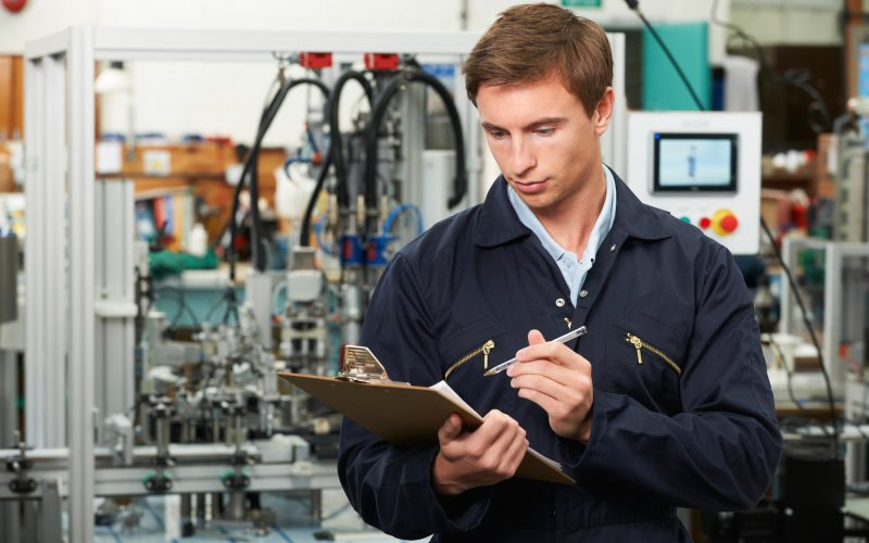 Engineer Writing On Clipboard In Factory